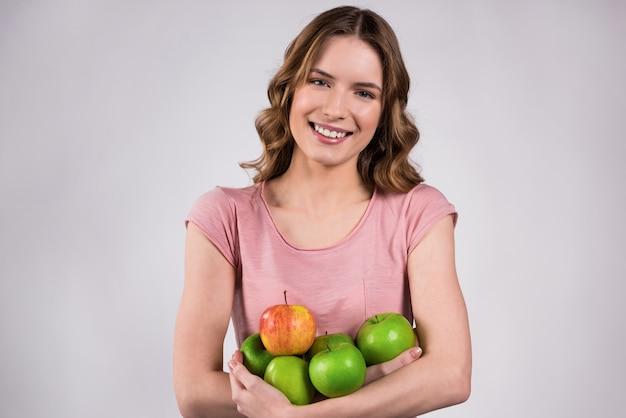Linda chica sonríe y sostiene deliciosas manzanas en sus manos.