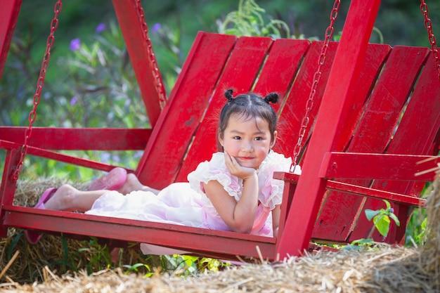 Linda chica sonriendo felizmente con un hermoso vestido rosa.