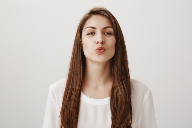 Linda chica sonriente doblando los labios y apoyándose en un beso