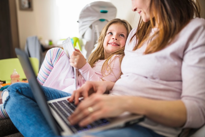 Linda chica sonriente mirando a su madre usando la computadora portátil
