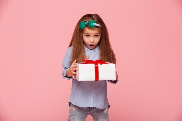 Linda chica sosteniendo la caja actual con la boca abierta, emocionado y sorprendido de recibir un regalo de cumpleaños