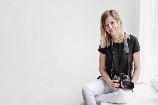 Linda chica sosteniendo un espacio de copia de foto de cámara