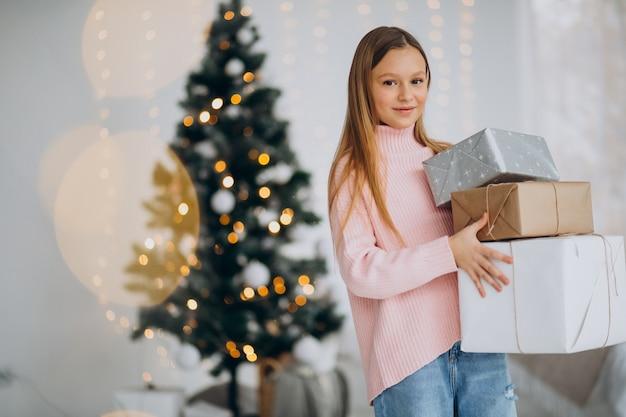 Linda chica sosteniendo regalos de navidad por árbol de navidad