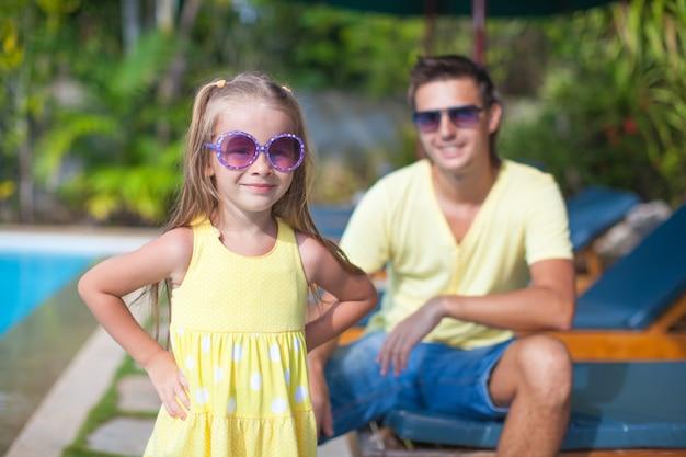 Linda chica con su joven papá cerca de la piscina