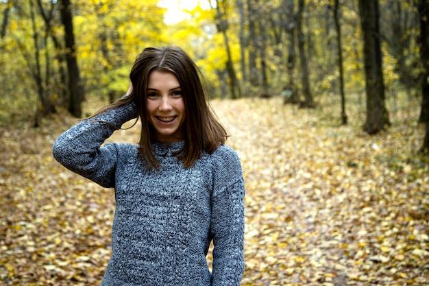 Linda chica en un suéter gris con tirantes en sus dientes se encuentra en la carretera en el bosque de otoño