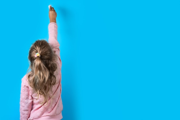 Linda chica con tiza blanca sobre un azul.