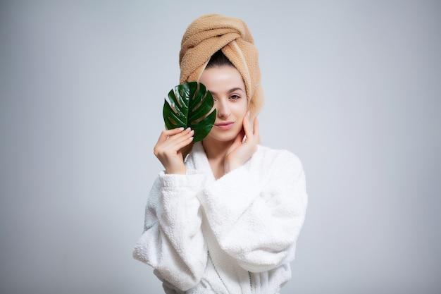 Linda chica con una toalla sobre su cabeza y una hoja verde después de tomar una ducha