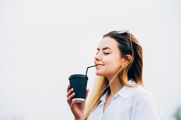 Una linda chica tomando café, sonriendo, los ojos cerrados, copia espacio