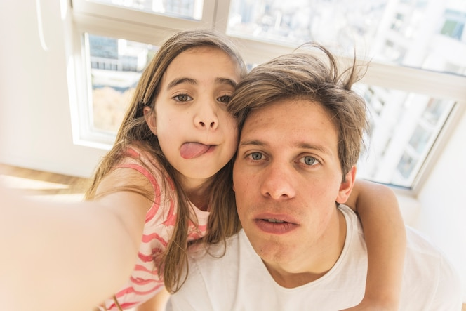 Linda chica tomando selfie divertido con su padre