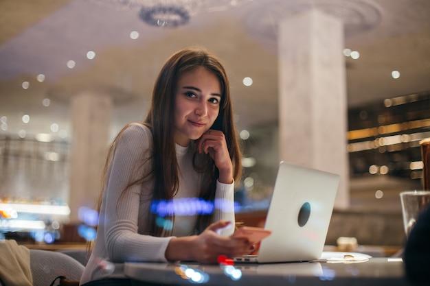 Linda chica trabaja en la computadora portátil en la cafetería hipster