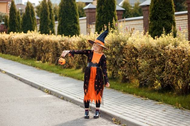 Linda chica con traje de carnaval de halloween con jack o lantern truco o trato al aire libre