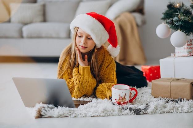 Linda chica usando computadora por árbol de navidad