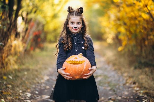 Linda chica vestida con disfraz de halloween al aire libre con calabazas
