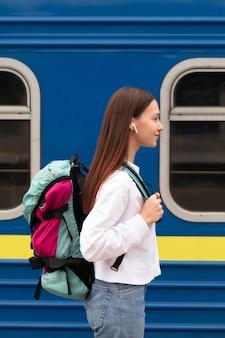 Linda chica de vista lateral en la estación de tren con mochila