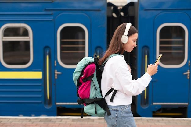 Linda chica de vista lateral en la estación de tren