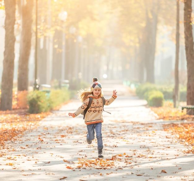 Linda colegiala corriendo en el parque