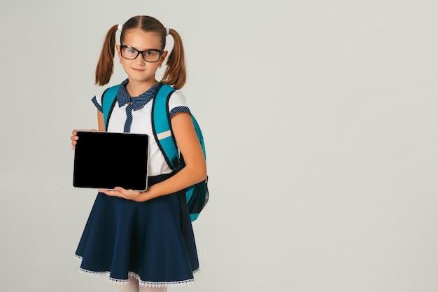 Linda colegiala con gafas tiene una tableta en manos sobre fondo gris