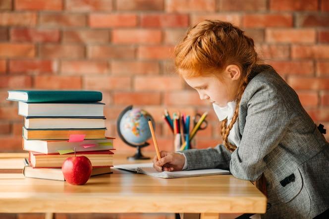 Linda colegiala haciendo los deberes en la mesa