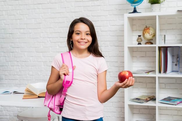 Linda colegiala de pie con mochila y manzana en el aula