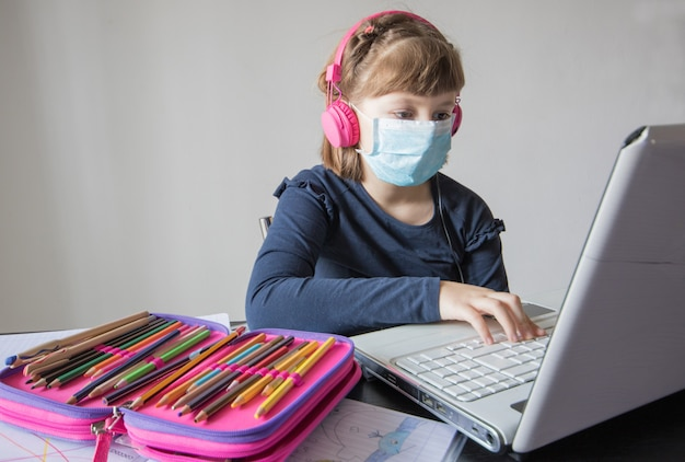 Linda colegiala que estudia matemáticas de tarea durante su lección en línea en casa, distancia social durante la cuarentena,