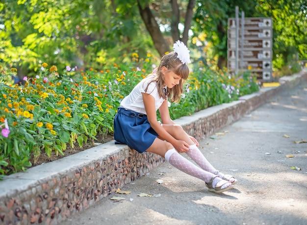 Una linda colegiala con uniforme escolar se sienta y endereza un calcetín en un parque de la ciudad.