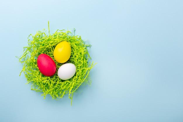 Linda composición de pascua. nido de papel con huevos de pascua multicolores sobre fondo azul. vista superior. copia espacio