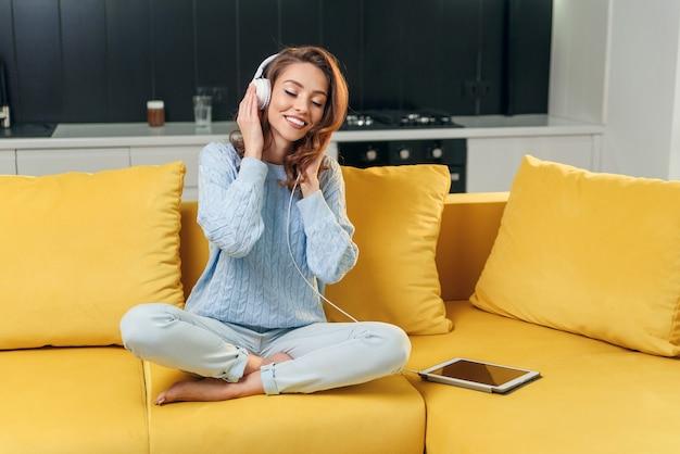 Linda dama con cabello castaño ondulado en suéter azul sentada en el cómodo sofá y disfrutando de agradables melodías en los auriculares en la cocina contemporánea.