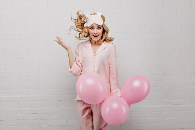 Linda dama caucásica en máscara de dormir saltando sobre pared blanca con globos de fiesta. sorprendida cumpleañera divirtiéndose en la mañana.