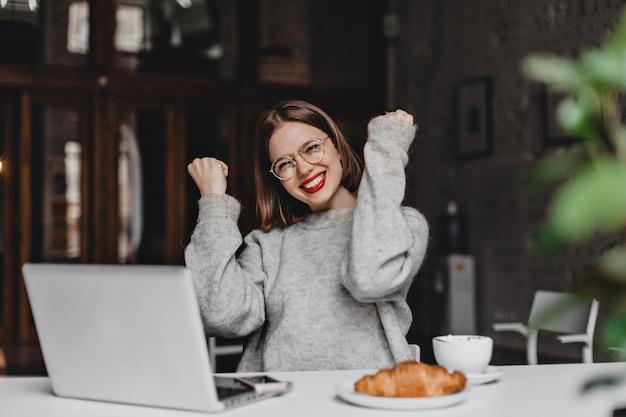 Linda dama con gafas disfruta del éxito, se ríe mientras está sentada en la cafetería con una computadora portátil gris y un apetitoso croissant.