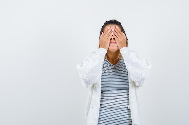 Linda dama manteniendo las manos en los ojos en camiseta, cárdigan y mirando emocionado, vista frontal.