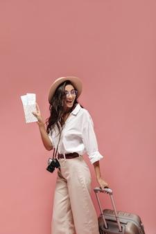 Linda dama rizada con cabello moreno en camisa blanca de manga ancha, pantalón beige con cinturón moderno y elegantes anteojos posando con boletos de avión