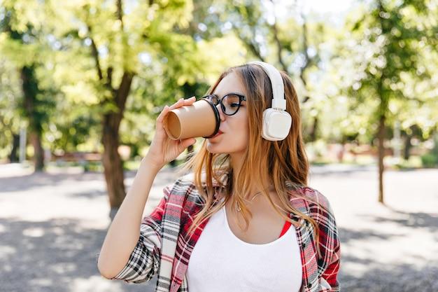 Linda dama tomando café con placer en la calle. encantadora modelo femenina en auriculares blancos de pie delante de los árboles.