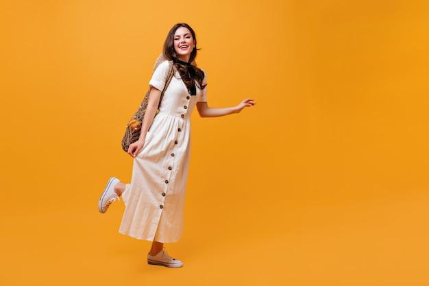 Linda dama en vestido midi con bolsa de hilo con frutas se mueve sobre fondo naranja.