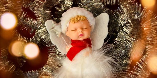 Linda decoración de navidad de ángel sobre fondo rojo. copie el espacio. tarjeta de felicitación. feliz navidad y año nuevo