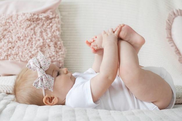 Linda y divertida niña rubia caucásica con arco en la cabeza acostado ob cama jugando con los pies sobre la superficie de almohadas decorativas en casa