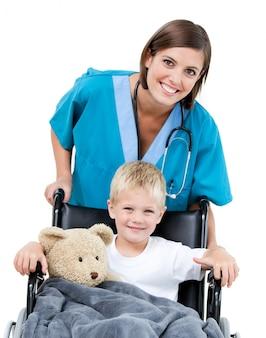 Linda doctora llevando adorable niño en el wheelchai