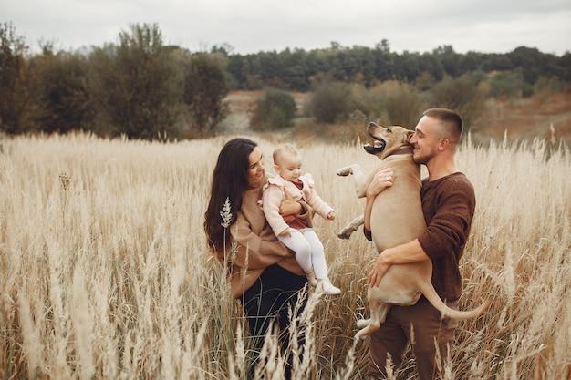 Linda y elegante familia jugando en un campo de otoño