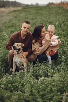 Linda y elegante familia jugando en un campo