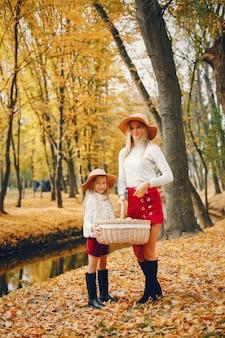 Linda y elegante familia en un parque de otoño