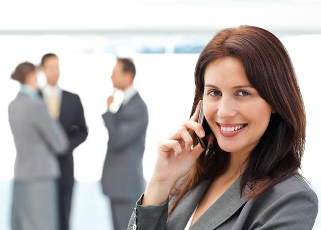Linda empresaria en el teléfono mientras su equipo discutiendo