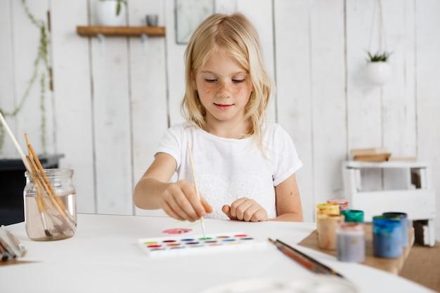 Linda y encantadora chica rubia con camiseta blanca pincel profundo en pintura