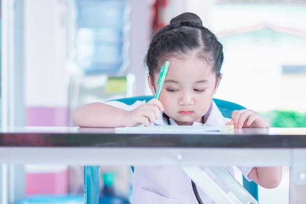 Una linda y encantadora niña asiática en uniforme de enfermera vestido escribiendo un informe