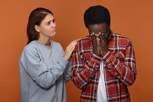 Linda esposa blanca joven compasiva consolando y consolando a su infeliz marido negro que está llorando debido a serios problemas en el trabajo. cuidadosa mujer europea apoyando a su novio africano