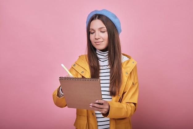 Linda estudiante con beaytiful sonrisa en una chaqueta amarilla con cuaderno