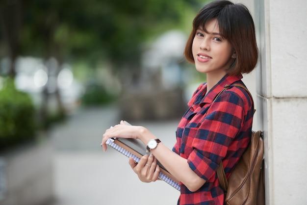 Linda estudiante con mochila y libros de texto apoyándose en la pared del edificio de la universidad