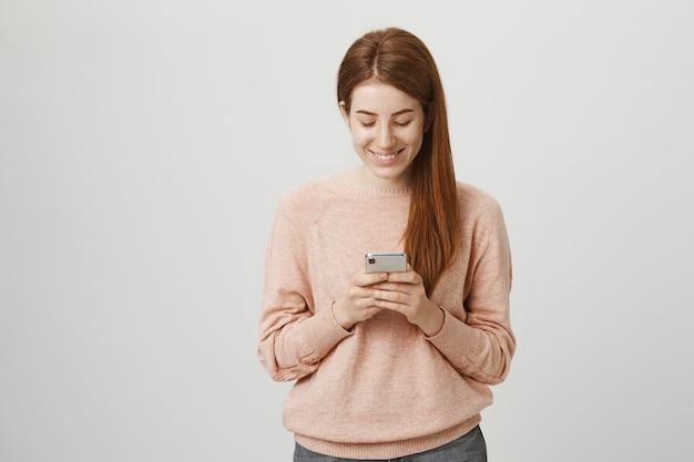 Linda estudiante pelirroja con teléfono móvil y sonriendo a la pantalla