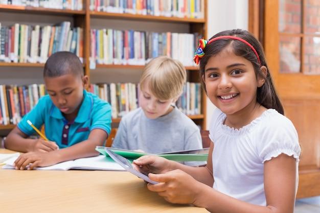Linda estudiante usando una tableta en la biblioteca