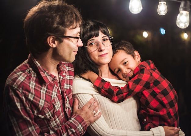 Linda familia bajo bombillas sesión de fotos de navidad