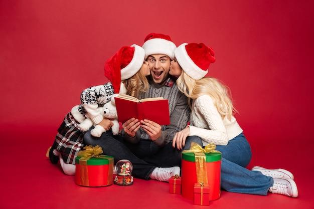 Linda familia joven con sombreros de navidad sentado aislado