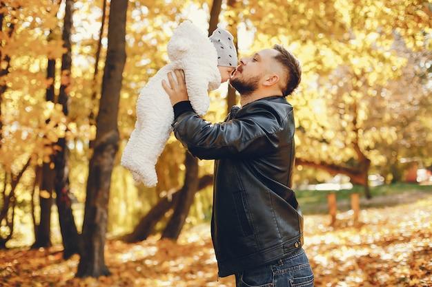 Linda familia jugando en un parque de otoño
